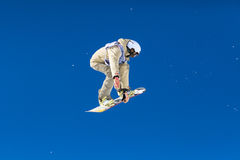 Beige Snowboarder Mid Air. Snowboarder competing in competition in Val Thorens, France Stock Photos