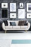 Minimal living room interior. Beige sofa against concrete wall with gallery of posters in minimal living room interior Royalty Free Stock Photography