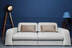 Beige Sofa in einem dunkelblauen Innenraum mit einer Lampe und einem Studioscheinwerfer lizenzfreie stockfotos