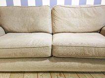 Beige sofa near the wall with striped wallpaper Royalty Free Stock Images