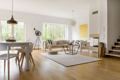 Multifunctional living room. Beige sofa with pillows in multifunctional living room with dining table and white chairs royalty free stock image