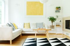 Beige sofa in warm interior. Candles on wood table and beige sofa with patterned pillows in warm interior with plant on stool and yellow painting on wall Stock Photo