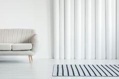 White living room with sofa. Beige sofa in white living room interior with striped rug and tubes wall with copy space stock photos