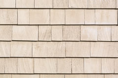 Beige stained cedar shingles. Close view of rows of beige stained cedar shingles on an exterior wall Stock Photo