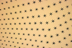 Beige Star Background. Black stars on a beige or manila background, their sizes tapering to provide a sense of perspective Royalty Free Stock Photos