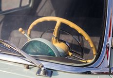 Beige steering wheel of a retro car is visible through the windshield Royalty Free Stock Image