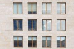Beige Steinwand mit vielen Fenstern Stockfotos