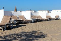 Beige StrandKlappstühle mit weißen Schirmen Stockfoto