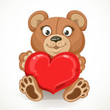 Beige teddy bear holding a heart Royalty Free Stock Photography