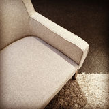 Beige textile armchair on a carpet Stock Photography