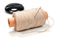 Beige thread on a cardboard spool with a needle and button on white background Royalty Free Stock Image