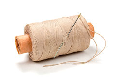 Beige thread on a cardboard spool with needle on white background Royalty Free Stock Photography