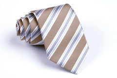 Beige tie rolled on white background Stock Photo