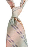 Beige tie on white. Closeup of pink beige tie with stripes and selective focus isolated on white Royalty Free Stock Photo