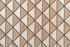Beige tiles wall or floor with light floral decoration. Repeating graphic design, flat surface, geometrical background.  royalty free stock image
