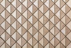 Beige tiles wall or floor with light floral decoration. Repeating graphic design, flat surface, geometrical background.  stock photography