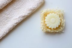 A beige towel and a soap in the form of a flower on a light background. Top view stock photo