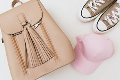 Beige Turnschuhe, Rucksack und rosa Kappe auf hellem Pastellhintergrund stockfotografie