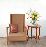Beige upholstered chair with side table Stock Images