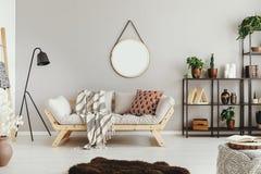 beige vägg i stilfull bohovardagsrum med den eleganta soffan och raserimatta arkivbilder