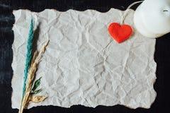 Beige verfrommeld document met hart, kaars en vernietigde bloem voor Royalty-vrije Stock Foto's