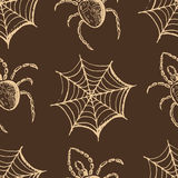 Beige webs and spiders on a brown background Stock Photos