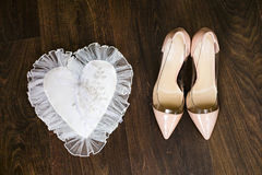 Beige wedding bridal shoes and gold wedding rings on white decorate pillow Royalty Free Stock Photos