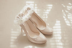 Beige wedding patent leather shoes. On light background with bride garter Royalty Free Stock Image