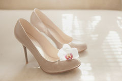Beige wedding patent leather shoes. On light background with orhid flower Stock Photos