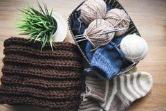 Beige, weißes und blaues Garn, Stricknadeln im Korb und ein brauner Schal lizenzfreies stockbild