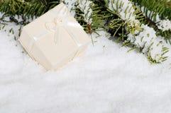Beige Weihnachtsgeschenk im Schnee Stockbild
