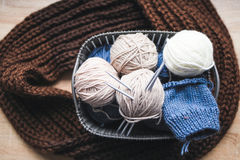 Beige, white and blue yarn, knitting needles in the basket and a brown scarf Royalty Free Stock Photography