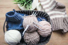 Beige, white and blue yarn, knitting needles in the basket. Striped beige-white knitted socks and a green plant in the pot Stock Photo