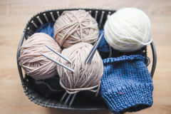 Beige, white and blue yarn, knitting needles in the basket Royalty Free Stock Photos