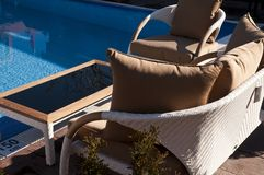 Wicker furniture sets by the pool. Beige wicker furniture sets by the pool with coffe table, closeup view royalty free stock image