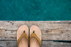 Beige wipschakelaarsandals op rand van houten dok over water Stock Afbeeldingen