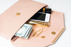 Beige woman's clutch handbag. Cosmetics, jewelry, money and smartphone in an open beige woman's clutch handbag on a white background Royalty Free Stock Images