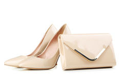 Beige women's high-heeled shoes. Pair of beige women's high-heeled shoes with handbag isolated on a white Royalty Free Stock Photo