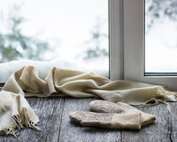 Beige woolen scarf and mittens located on wooden window sill. Beige woolen scarf and mittens located on stylized wooden window sill. Winter concept of comfort Royalty Free Stock Images