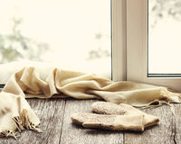 Beige woolen scarf and mittens located on wooden window sill. Beige woolen scarf and mittens located on stylized wooden window sill. Winter concept of comfort Stock Photo