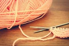 Beige yarns and knitting needles. Toned image Royalty Free Stock Photo