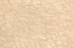 Beige yttersida som göras av de grova penselföringarna av murbruk som en bakgrund royaltyfria bilder