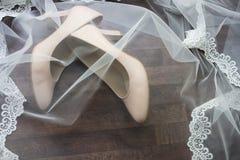 Beigea brud- skor täckas med en skyla Arkivfoton