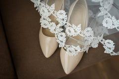 Beigea brud- skor täckas med en skyla Arkivbilder