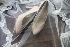 Beigea brud- skor täckas med en skyla Arkivfoto