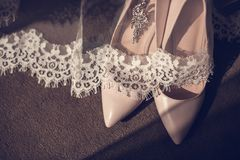 Beigea hög-heeled skor piskar kvinnors skor på glansiga skor för en hälshoesBride för träbackgroundlight och en liten buket arkivfoton