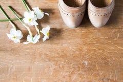 Beigea läderskor med ortopediska innersulor och vita påskliljor Royaltyfria Foton