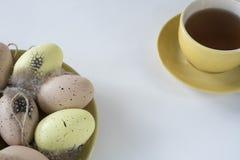 Beigea, rosa och gula påskägg på plattan, med koppen kaffe, på den vita tabellen fotografering för bildbyråer