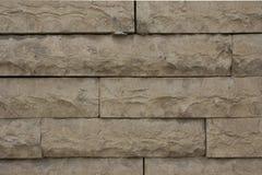 Beigea stenar för stads- vägg utanför en byggnad arkivfoton