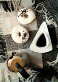 Beignet avec le glaçage blanc et la belle tasse blanche avec le pot de café sur le fond du plaid scandinave, concept de petit déj photographie stock